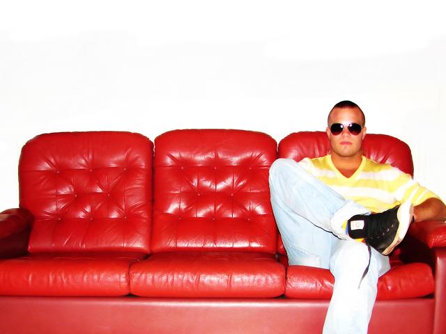 mladý muž sedící na červené pohovce